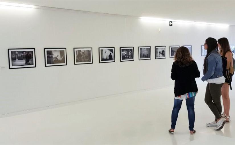 Esta imagen muestra el Hall de la Facultad de Comunicación de la Universidad San Jorge donde se encuentran las dos estudiantes creadoras de la exposición junto con la responsable de las Actividades Culturales de la misma universidad.