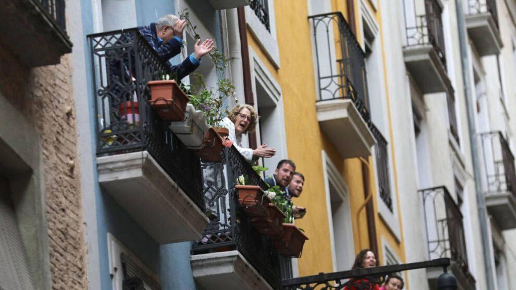 Un edificio con balcones, gente en ellos aplaudiendo.