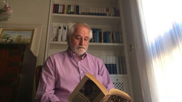 Rafael Larraz leyendo un libro de Irvin Stone frente a alguno de los libros de su biblioteca incluidas una colección de enciclopedias