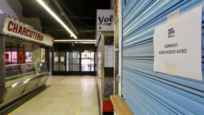 """Los puestos de los mercados se encuentran con la persiana bajada con carteles de """"Cerrado hasta nuevo aviso"""""""