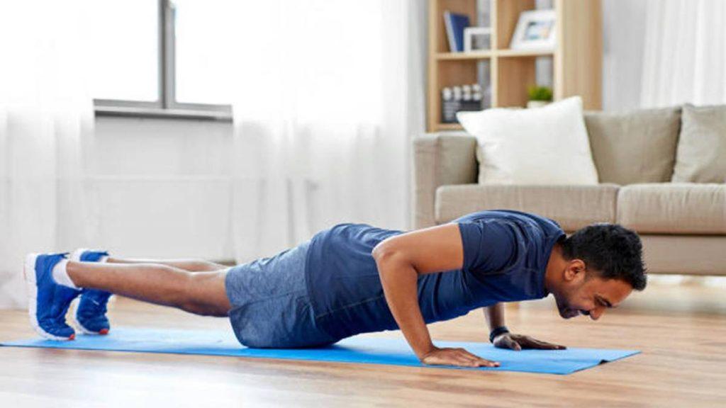 Hombre haciendo flexiones sobre una esterilla en el salón de su casa. Es un ejemplo de lo que muchos ciudadanos se han visto obligados a hacer durante el confinamiento.