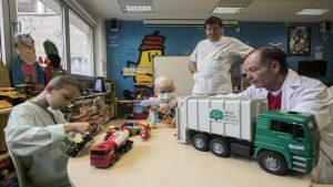 Un niño enfermo en el Aula Hospitalaria del Hospital Miguel Servet jugando con un camión de reciclaje junto a dos de los profesores del aula.