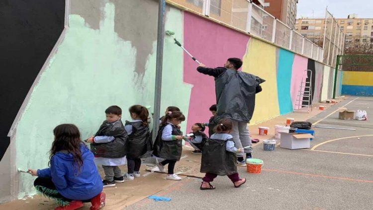 Niños del Colegio La Salle Montemolín pintando el mural solidario en el patio junto a uno de los voluntarios de Believe in Art